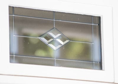 Stained glass overlay forming part of double glazing unit - introduced by owners for aesthetic appeal